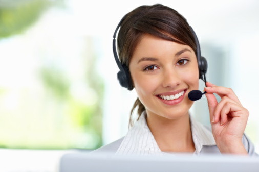 Pretty female employee speaking on headset
